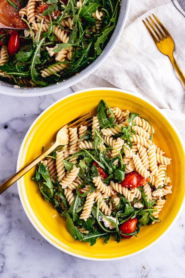 Overhead shot of roasted tomato pasta salad in a yellow bowl with a gold fork