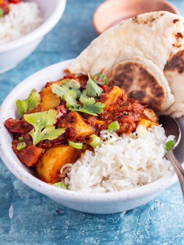 White bowl of halloumi curry with potato with rice and naan on a blue background