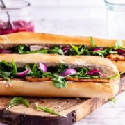 Side on photo of tofu sandwich with pickled onions and rocket