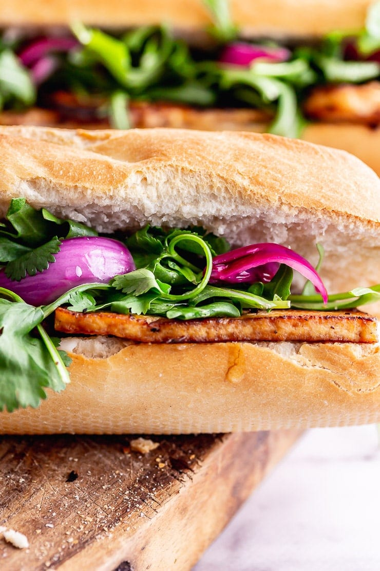 Close up of tofu sandwich with pink pickled onions in a baguette
