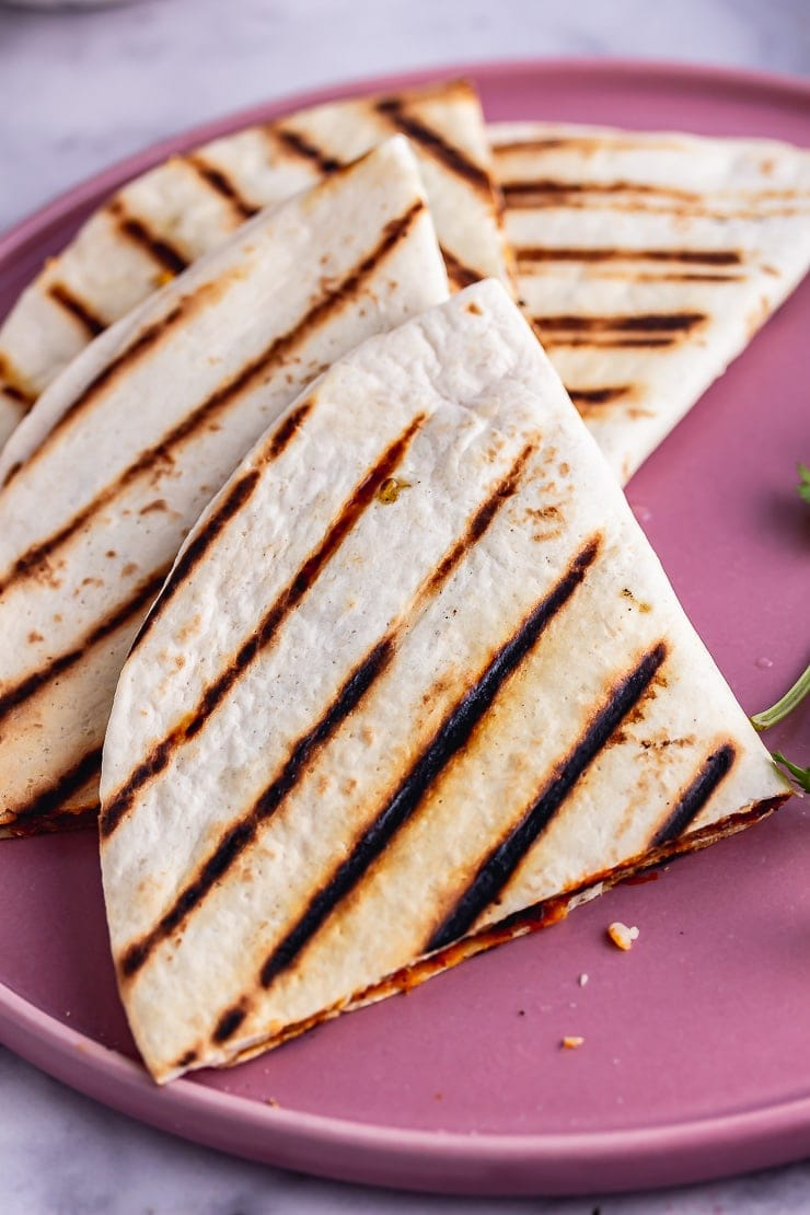 Close up of a vegetarian quesadilla on a pink plate