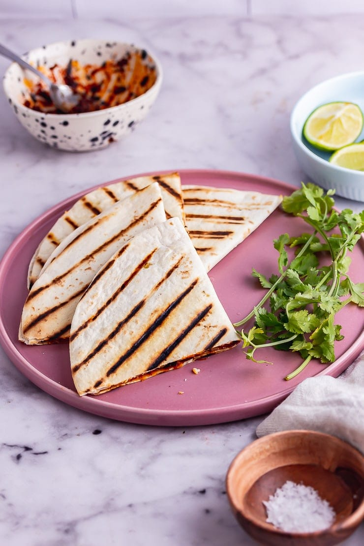 Vegetarian quesadilla quarters on a pink plate over a marble background
