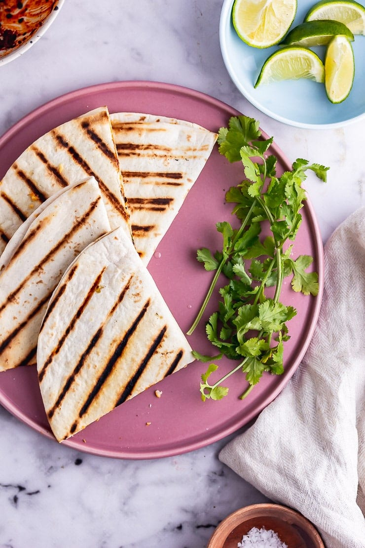 Overhead shot of a vegetarian quesadilla on a pink plate with lime and salt
