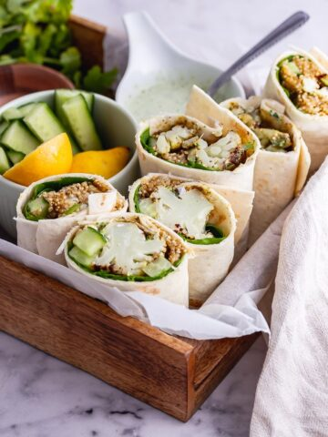 Veggie wraps in a wooden tray on a marble background