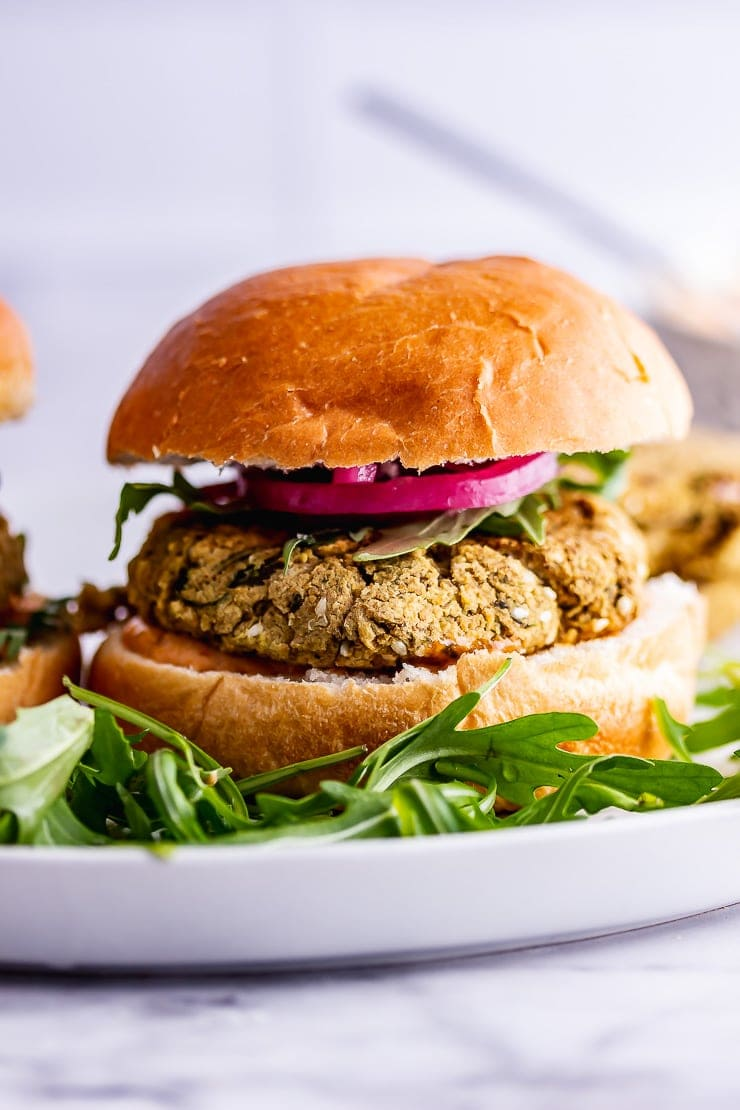 Side on shot of baked falafel burger with rocket and pickled onions