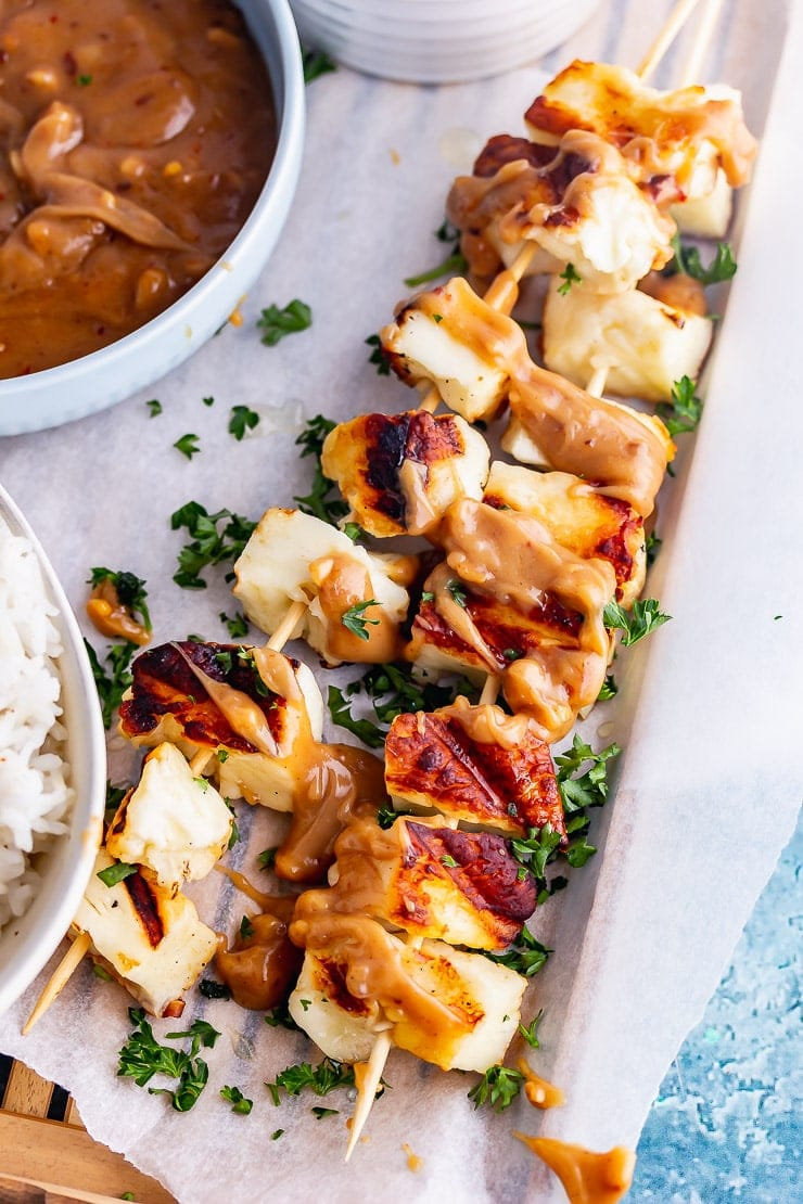 Grilled halloumi skewers drizzled with peanut sauce and fresh herbs