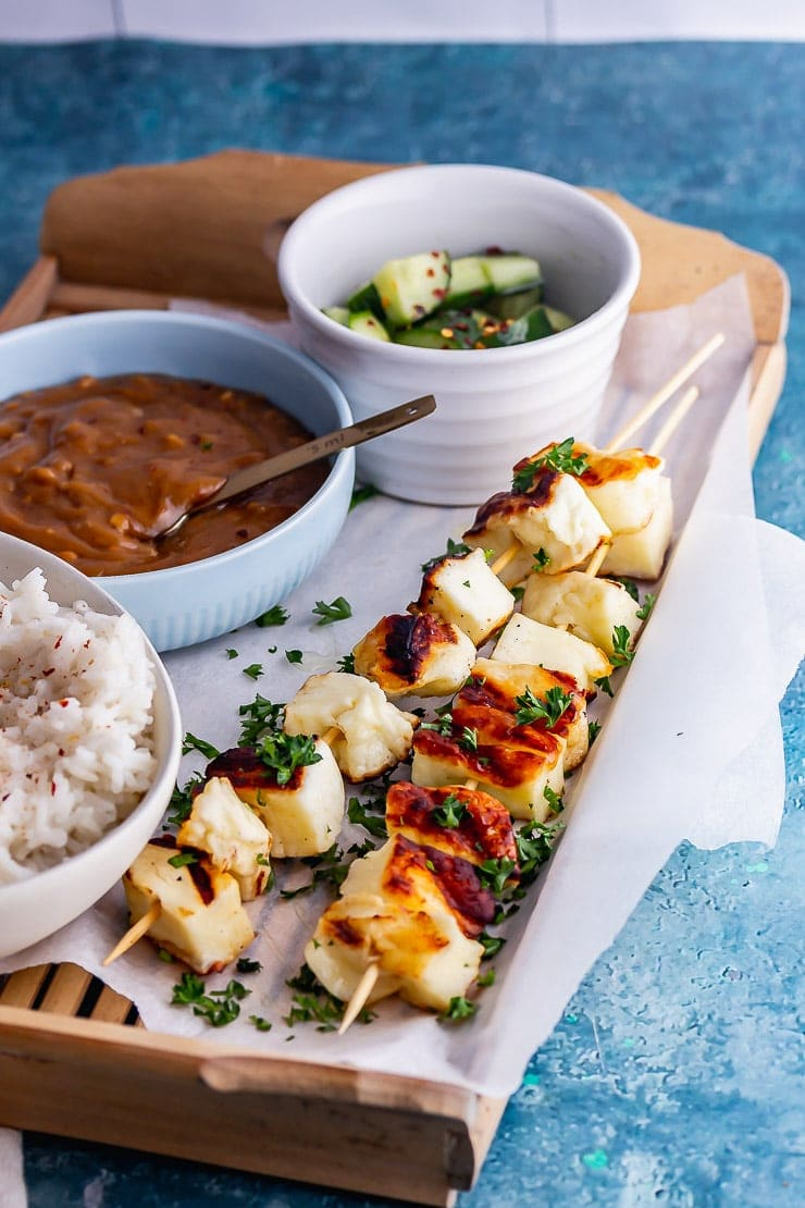 Halloumi skewers with satay sauce and cucumber on a wooden tray