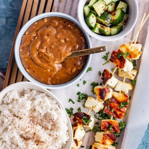 Overhead shot of grilled halloumi skewers with satay sauce, cucumber salad and rice on a wooden tray