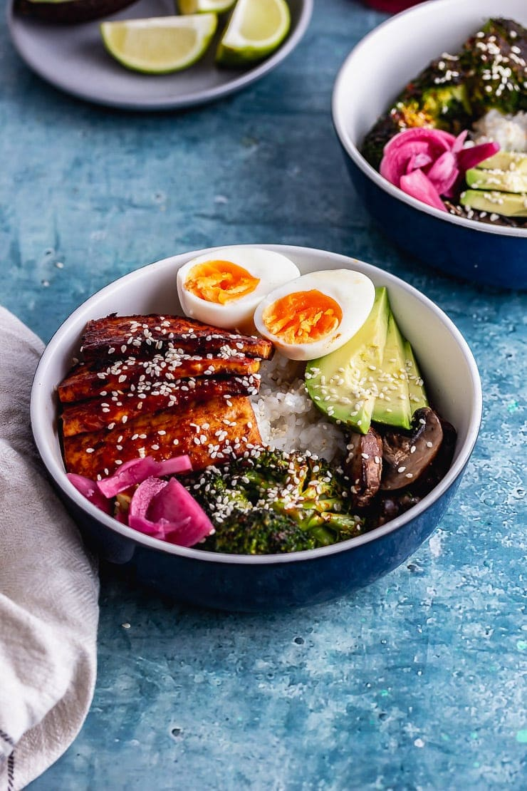 Korean baked tofu in a rice bowl with avocado and egg on a blue surface