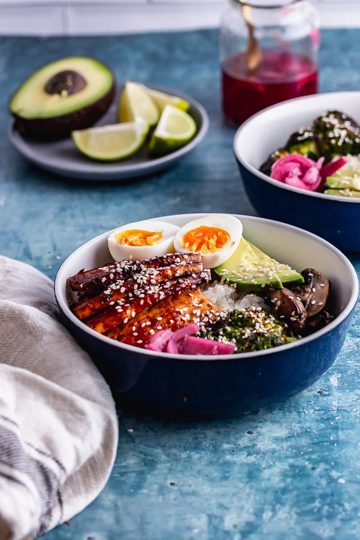 Side on shot of Korean baked tofu rice bowls in a blue bowl with avocado