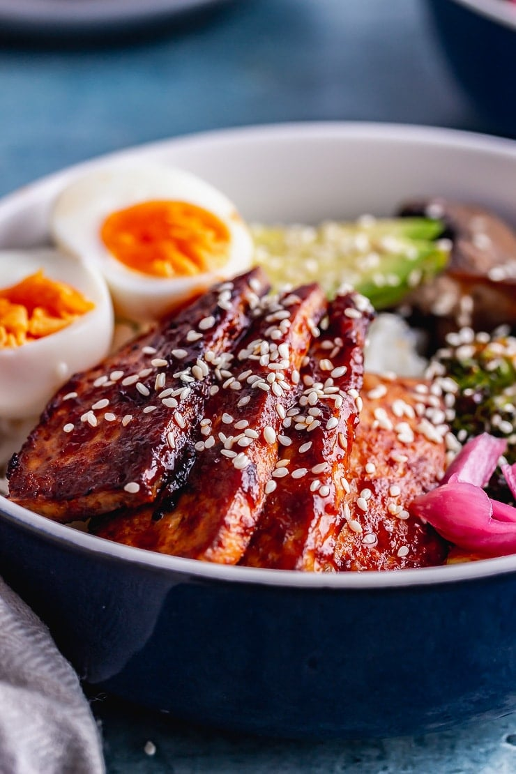 Close up of Korean baked tofu with boiled eggs on rice in a blue bowl