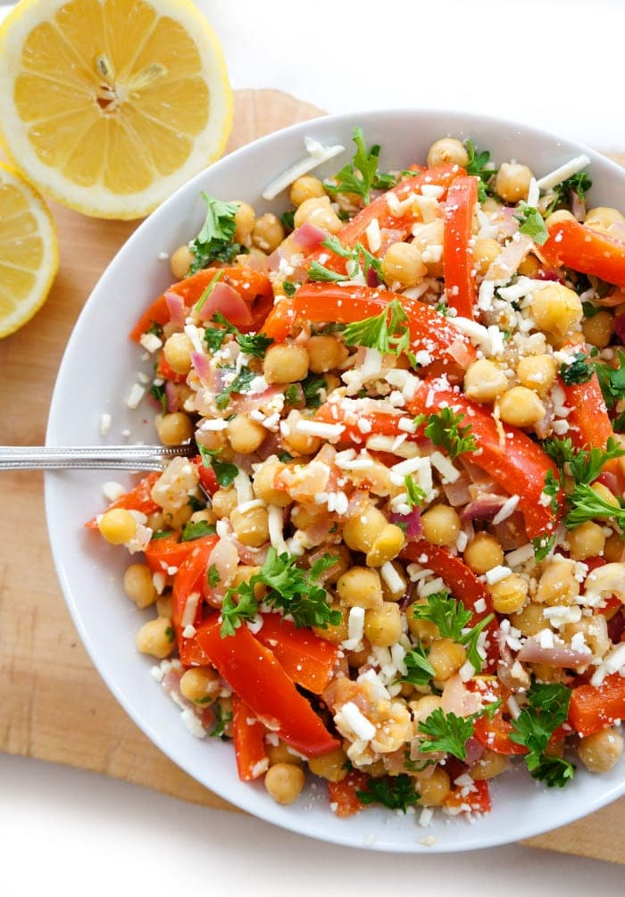 Overhead shot of Mediterranean chickpea salad in a white bowl with lemon
