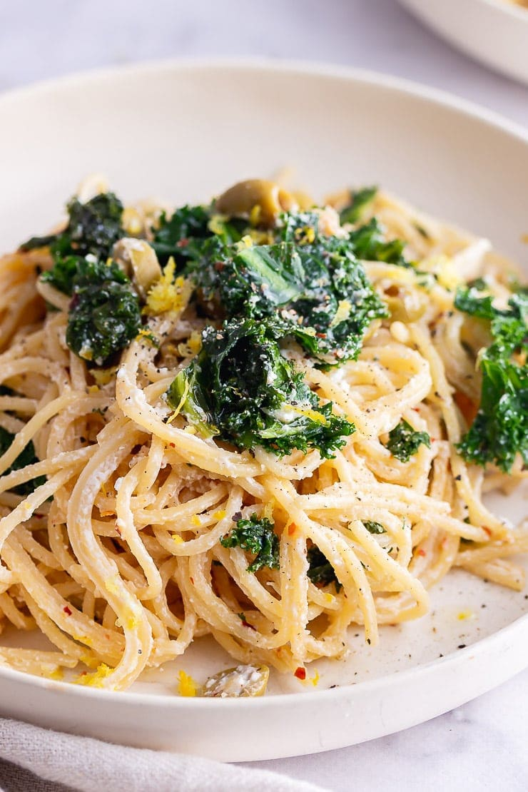 Close up of garlic spaghetti with kale in a white bowl