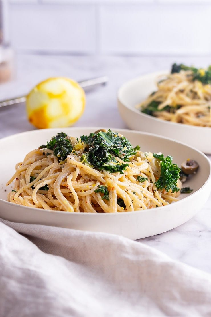 Side on shot of roasted garlic spaghetti with kale in a white bowl on a marble surface