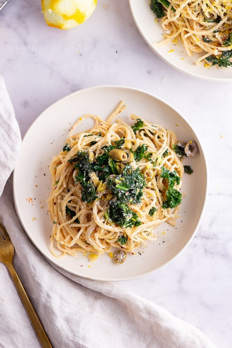Overhead shot of garlic spaghetti with kale on a marble surface