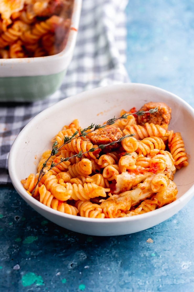 White bowl of veggie sausage pasta bake on a blue background