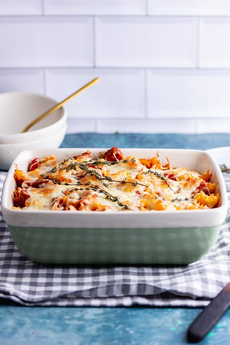 Side on shot of vegetarian sausage pasta bake in a green dish on a checked cloth