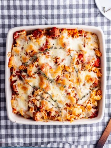 Overhead shot of vegetarian sausage pasta bake on a checked cloth