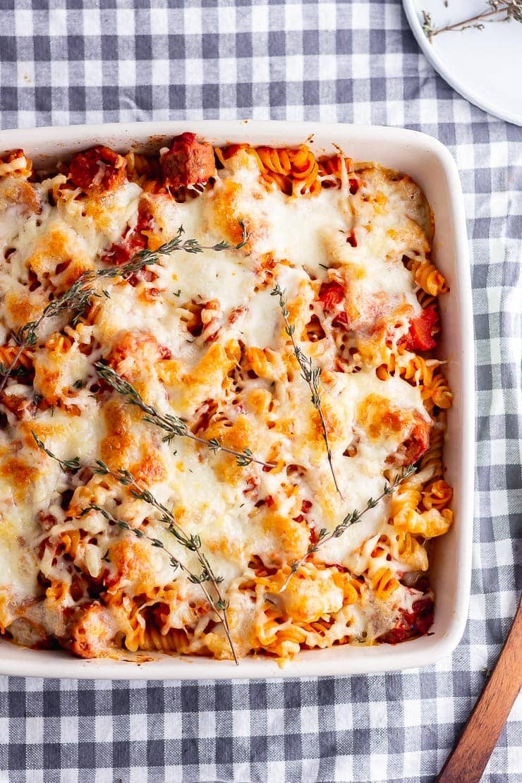 Overhead shot of vegetarian sausage pasta bake on a grey checked cloth
