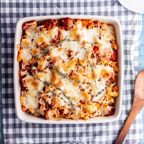 Overhead shot of vegetarian sausage pasta bake on a checked cloth with wooden spoon