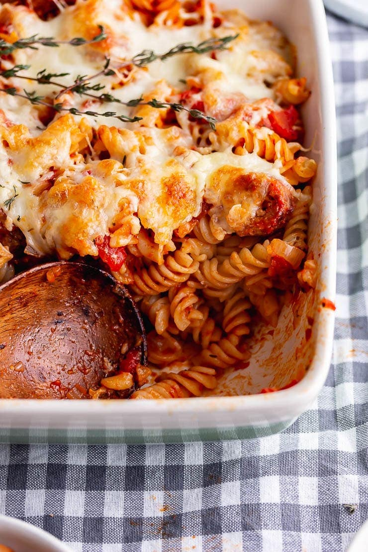 Wooden spoon with a portion take from sausage pasta bake on a checked cloth