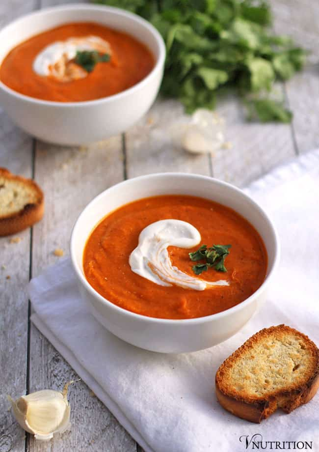 White bowl of tomato and chickpea soup on a white cloth with bread