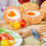 Scotch eggs on a wooden board