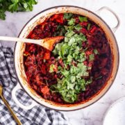 Overhead shot of bean chilli in a white pot with herbs and a checked cloth