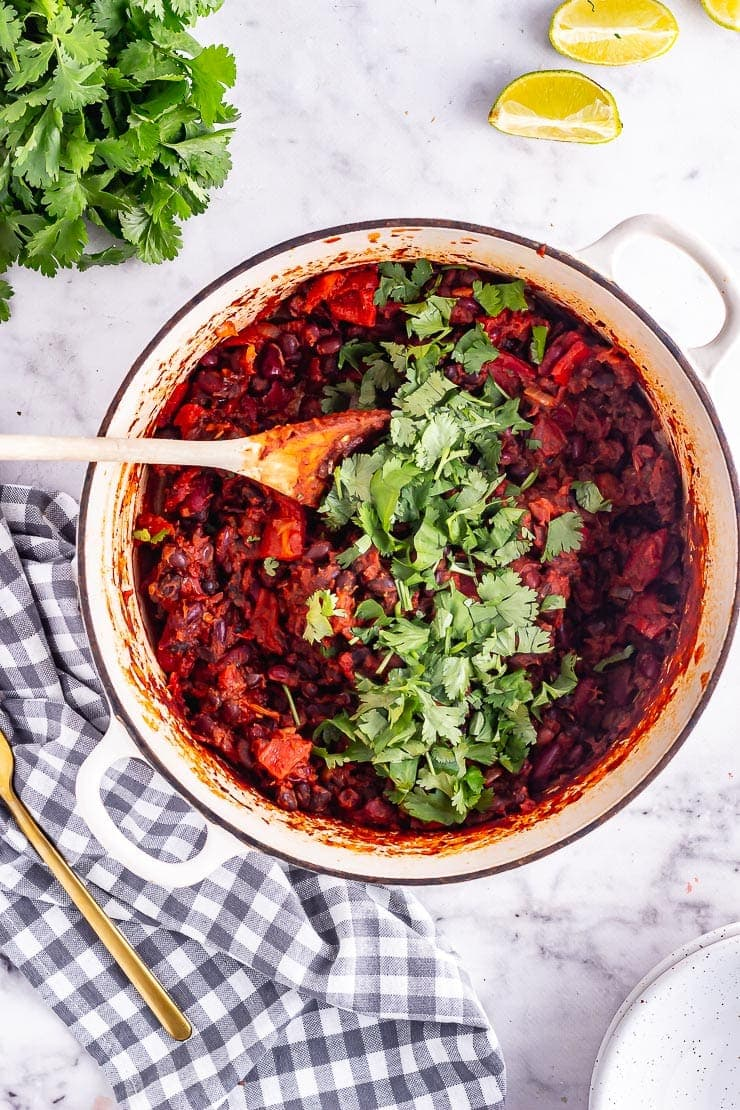 Overhead shot of bean chilli with coriander on a checked cloth