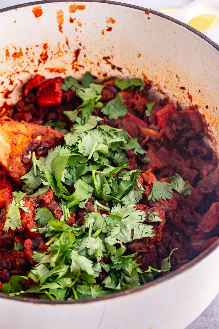 Close up of bean chilli in a white pot with chopped herbs and a wooden spoon
