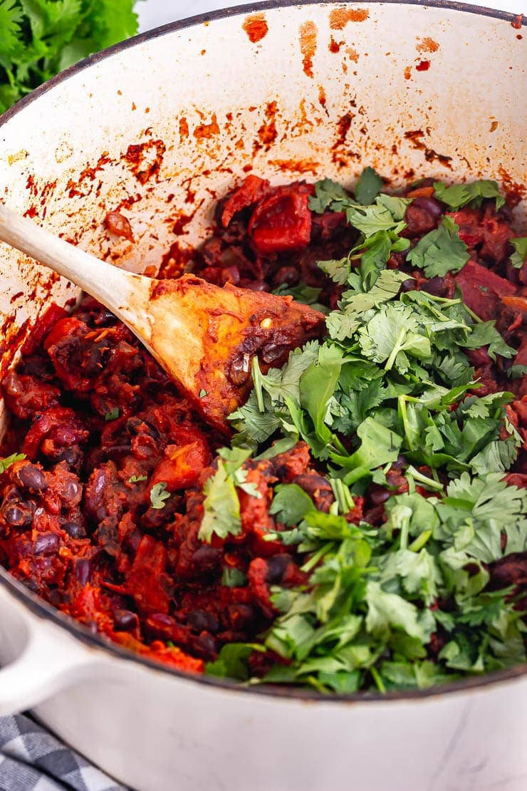Close up of bean chilli in a white pot with chopped herbs