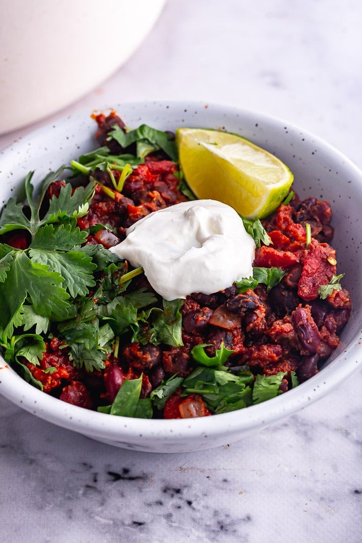 Close up of bean chilli in a white bowl with lime and coriander