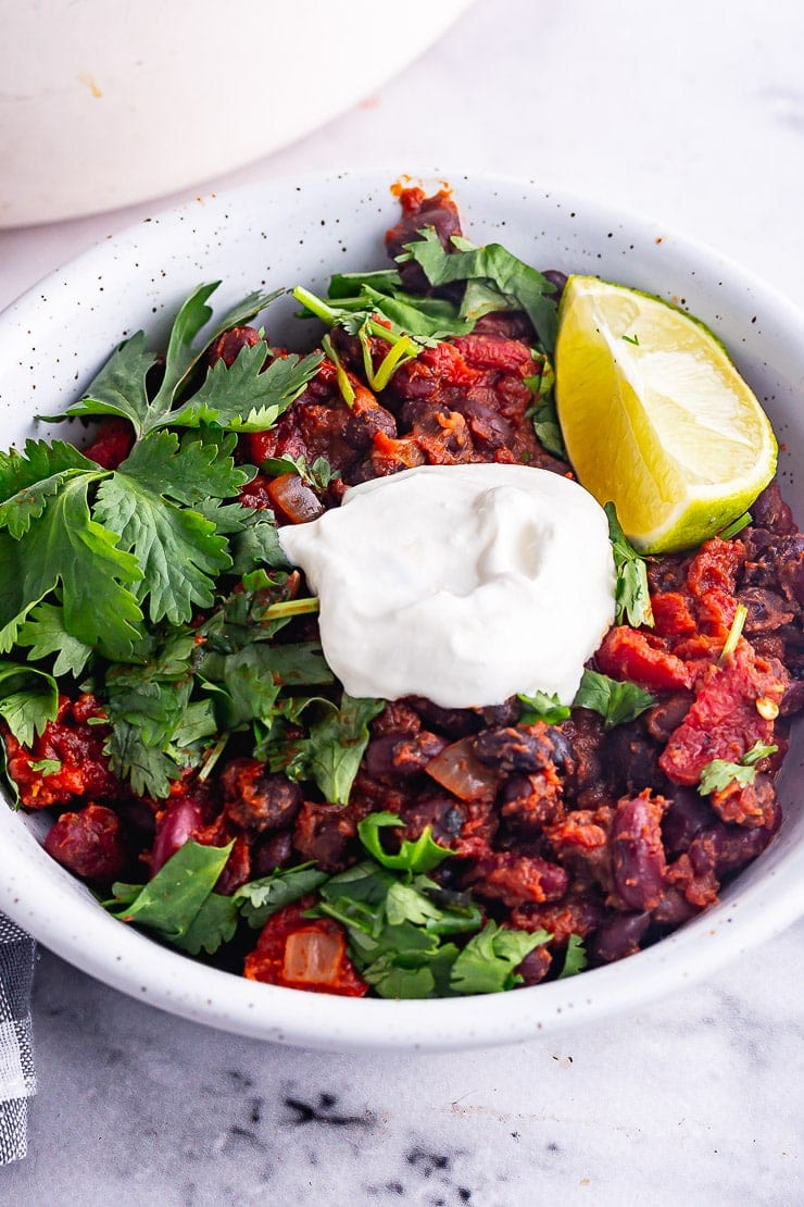 Close up of bean chilli in a white bowl with sour cream and lime and coriander