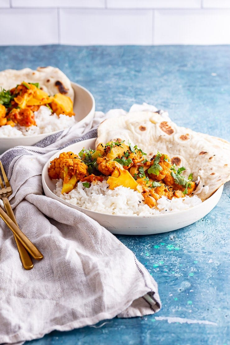 Side on shot of cauliflower and chickpea curry in white bowls on a blue surface