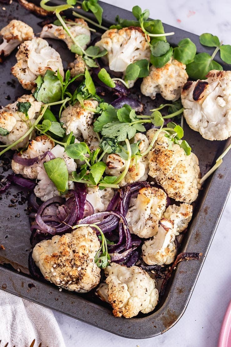 Overhead shot of roasted cauliflower and onions with greens on a baking sheet