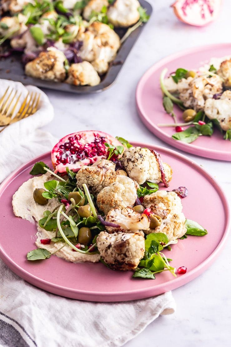 Pink plates of cauliflower salad with hummus and greens on a marble background