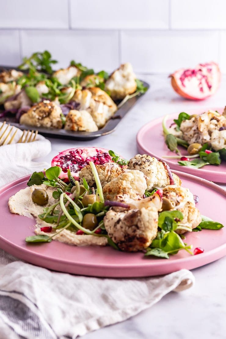 Side on shot of cauliflower salad on a pink plate on a beige cloth