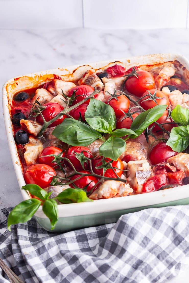 Baked vegetables and fish with tomatoes and basil on a marble surface