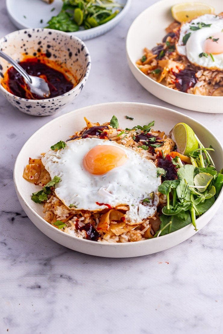 White bowl of kimchi fried rice topped with a fried egg with greens