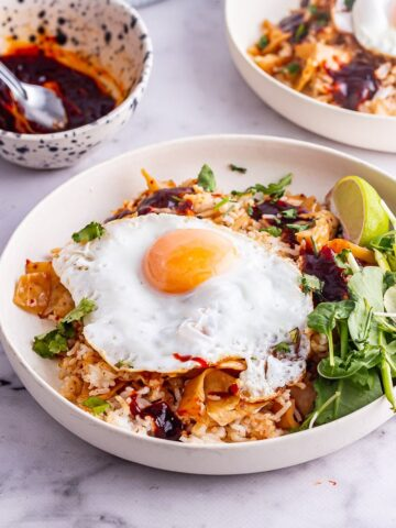 Cream bowl od kimchi fried rice with a fried egg and greens