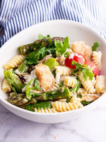 White bowl of mackerel pasta salad with asparagus and cherry tomatoes on a marble surface