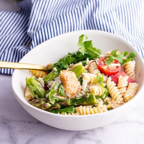 White bowl of mackerel pasta salad on a marble background with a gold fork
