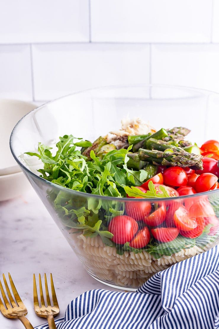 Glass bowl of mackerel pasta salad with asparagus and tomatoes with gold forks