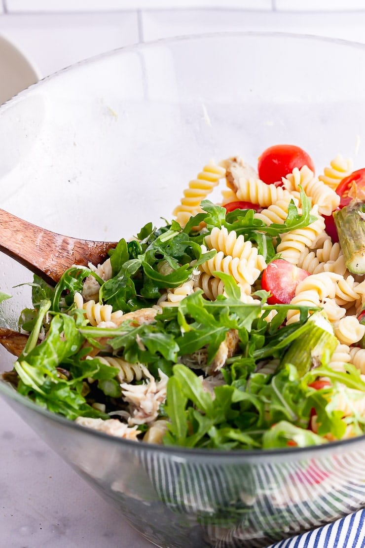 Close up of mackerel pasta salad in a glass bowl with a wooden spoon