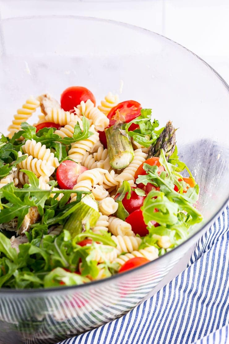 Close up of mackerel pasta salad in a glass bowl with tomatoes and rocket
