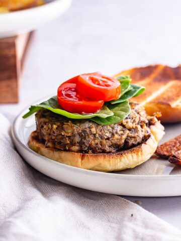 Side on shot of a mushroom burger on a grey plate on a marble background