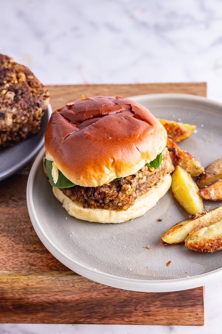 Mushroom burger with chips on a grey plate on a wooden box