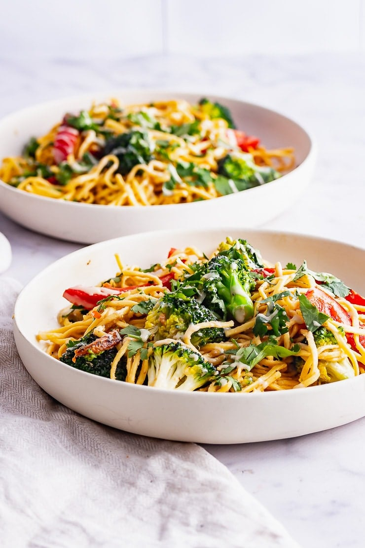 Side on shot of bowls of noodle salads with a beige cloth
