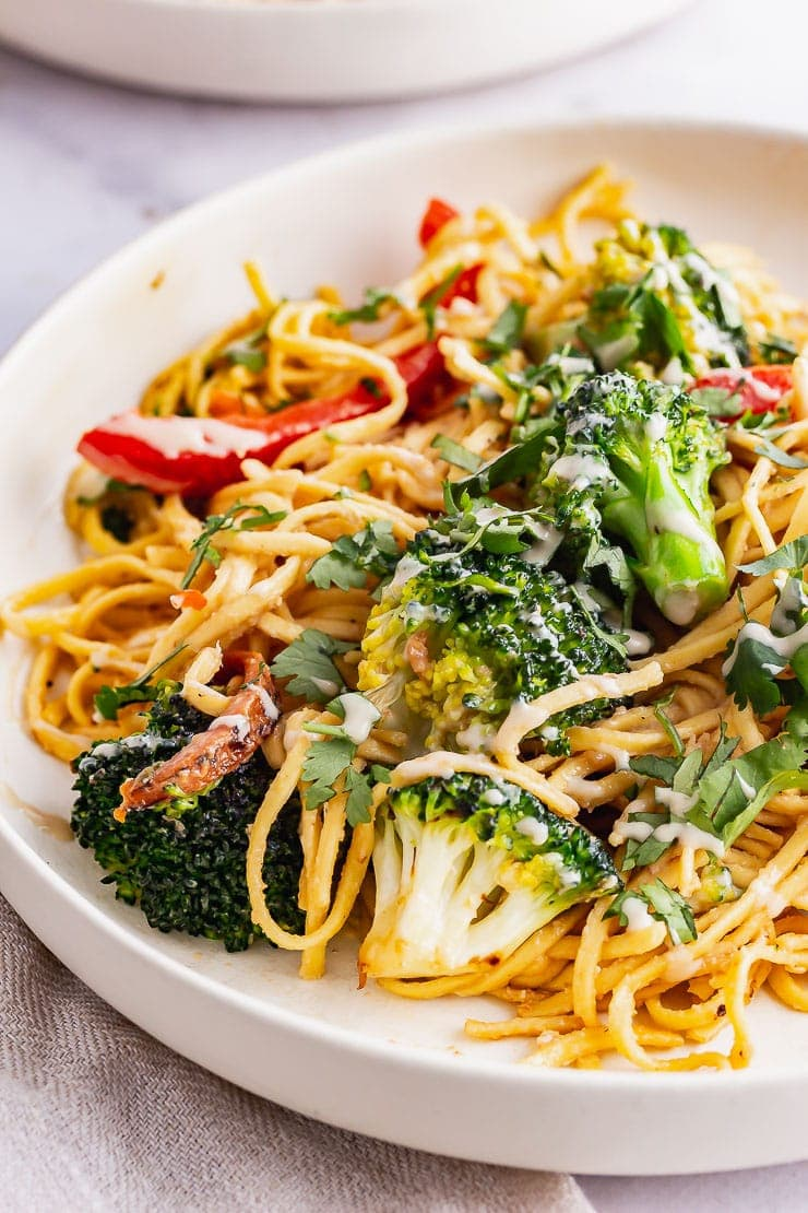 Close up of noodle salad with broccoli in a cream bowl