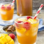 Raspberry mango iced tea in a glass with a straw